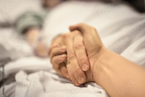 Carta da parati Man holding hand, giving support and comfort to woman, loved one sick in hospital bed