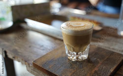 Billede på lærred Close up hot coffee  latte in transparent glass on timber table