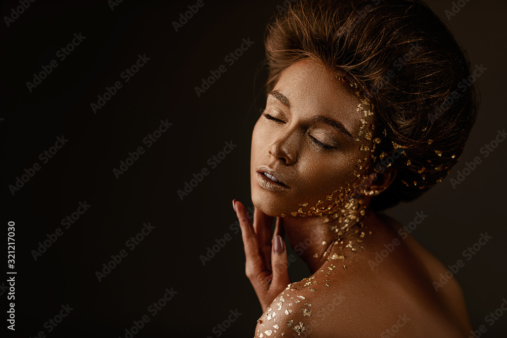Fashion art portrait of model girl with holiday golden shiny professional makeup. beaty woman with gold metallic body and hair on dark background. Gold glowing skin. copy space <span>plik: #321217030 | autor: producer</span>