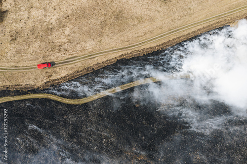 Valokuva Field fire and red fire truck near firebreak, aerial top down view
