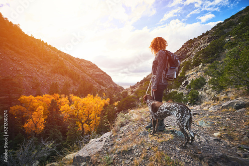 Платно a young woman and her dog hiking to the top of a mountain