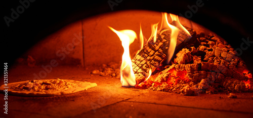 Baked tasty margherita pizza in Traditional wood oven in Naples restaurant, Italy. Original neapolitan pizza. Red hot coal.