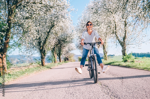 Happy smiling woman rides a bicycle on the country road under the apple blossom trees