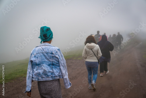 Obraz na płótnie Back view of refugees walk to the border in a cold day under fog