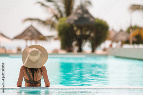 Stampa su Tela Woman relaxing by the pool in a luxury hotel resort enjoying perfect beach holid