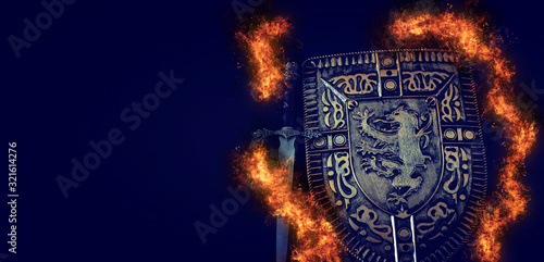 Fototapeta photo of shield knight armor and sword in fire flames over dark background