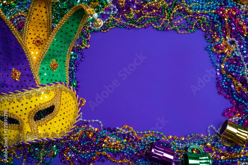 Photo Colorful Mardi Gras mask on purple background with beads