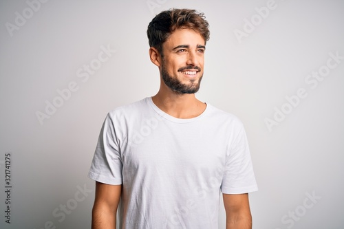 Fotografia Young handsome man with beard wearing casual t-shirt standing over white background looking away to side with smile on face, natural expression