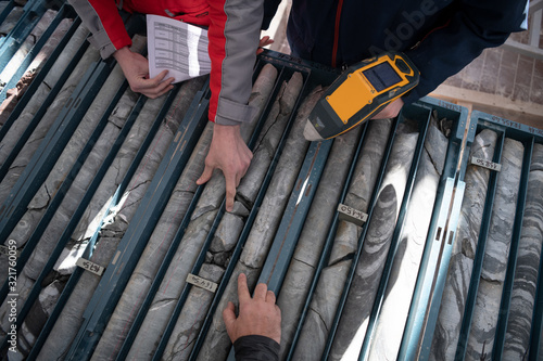 Fotografiet team of mining  workers measuring drilled rock core