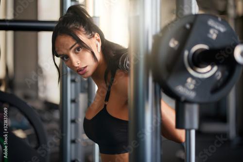 Foto Fitnesswoman training in smith machine.