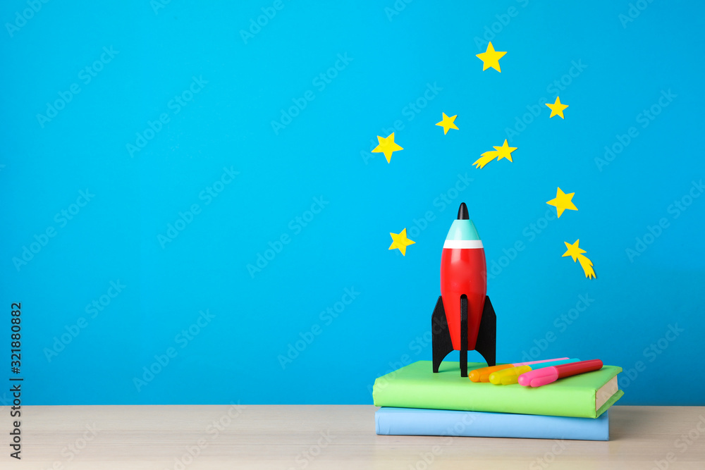 Bright toy rocket and school supplies on wooden desk. Space for text