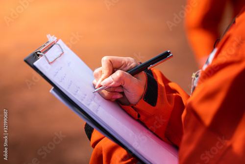 Wallpaper Mural Safety officer/Supervisor is writing note on the checklist paper during perform audit and inspection in oil field operation