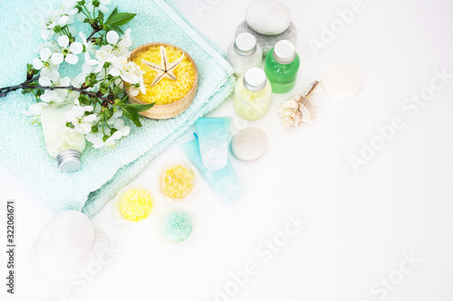 Care of a body. Aromatic salt for Spa therapies, cosmetics for a body and acceptance of bathtubs, towel and a spring flower on white background