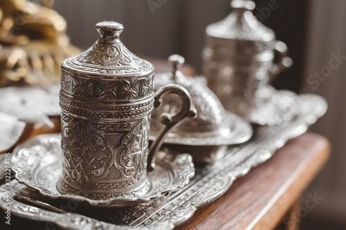Fototapeta Closeup shot of an antique silver tea set with a blurry background