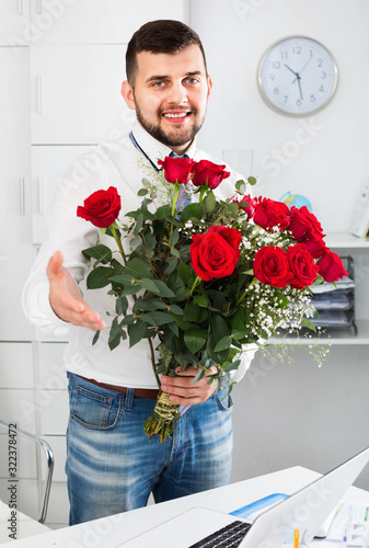 Leinwand Poster Young man ready to present flowers to woman