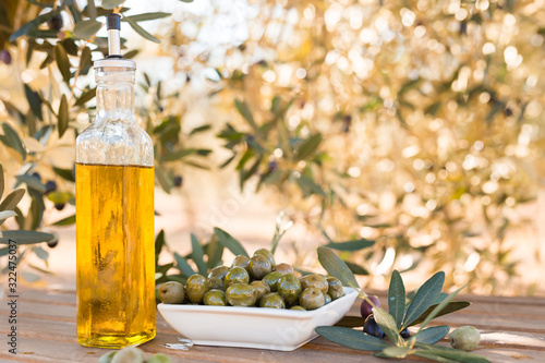 green olives and oil on table in olive grove Fototapeta