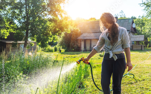 Fotografija Hipster young woman watering plants a country house, summer and garden care, org