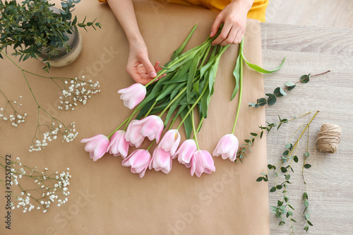 Unrecognizable young woman wearing mustard yellow shirt making a beautiful bouquet of flowers. Female florist at work concept. Close up, copy space, background.