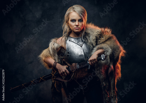 Fantasy woman knight wearing cuirass and fur, holding a sword scabbard ready for a battle Fotobehang