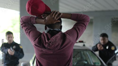 Fotografia, Obraz Shot back african american offender in mask stand hands up in patrol car in hand