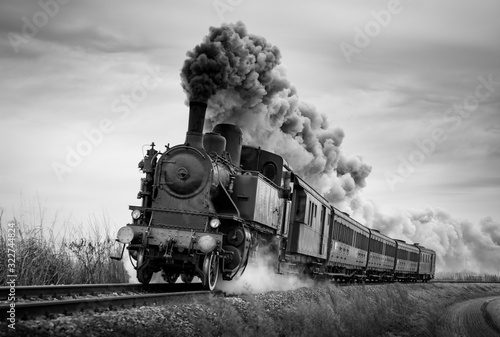 Steam train runs on the tracks on a cloudy day. Black and white photography.