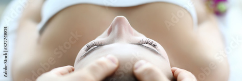 Male masseur hand make face massage young caucasian woman against spa cabinet background portrait. Beauty wellness concept
