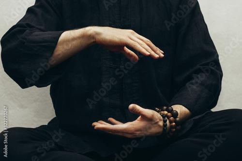 A man in black shirt sitting and doing qigong Fototapet