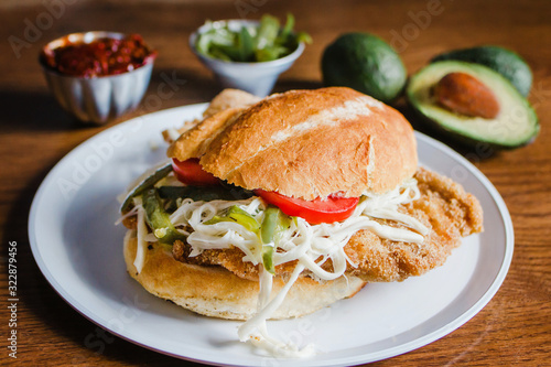 Fototapeta Mexican torta is chicken milanese sandwich with avocado, chili chipotle and oaxa