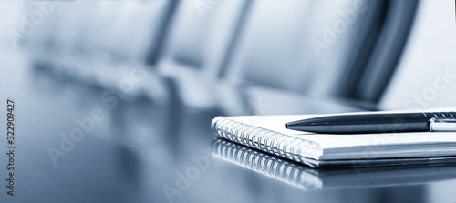Foto Notepad on a table with pen before meeting, blue tone, business concept with cop