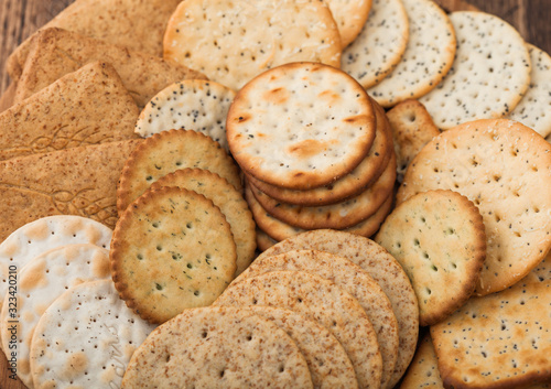Fényképezés Various organic crispy wheat, rye and corn flatbread crackers with sesame and salt in round plate on wooden background