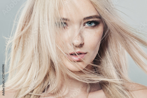 Tela Beautiful blonde woman with long healthy blowing hair and natural skin
