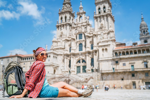 Fotografering Young female backpacker piligrim sitting on the Obradeiro square (plaza) in Santiago de Compostela, Spain