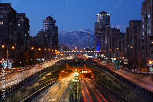 An Expressway and Underground tunnel in Tehran and a long exposure View of of mountains at the front just after the sunrise.