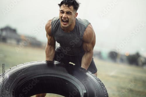 Obraz na plátne Strong sportsman doing a tire flip exercise