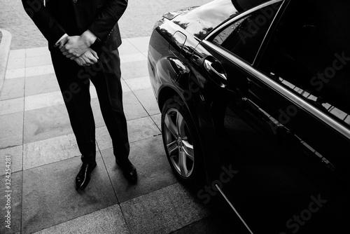 Fotografie, Obraz Valet's Hand Opening Grey Car Door On Street