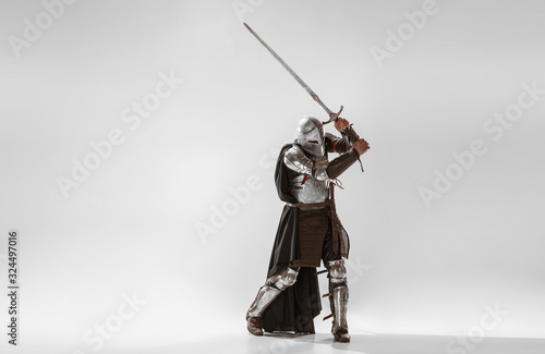 Fototapeta Brave armored knight with professional weapon fighting isolated on white studio background