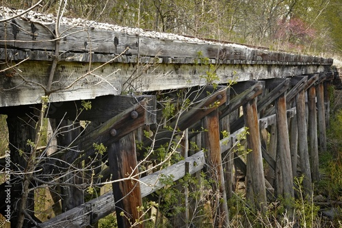 Canvas Print Closeup of an old wooden railroad bridge trestle surrounded by greenery in a for