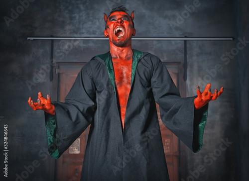 Valokuva Terrible devil man screaming. Scary Halloween scene
