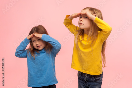 Portrait of funny amusing two little girls holding hands over eyes and looking far away with curious attentive expression, searching, viewing distance. indoor studio shot isolated on pink background