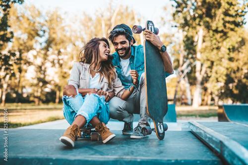 Beautiful young couple enjoying outdoors in city skateboarding park