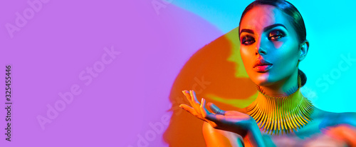 High Fashion model woman portrait in colourful bright neon lights, beautiful party girl with trendy make-up, manicure, hairstyle. Pointing hand, advertising gesture over colorful vivid background.