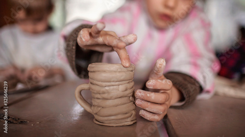 Fotografia Cute little kids playing together with modeling clay in pottery workshop, craft
