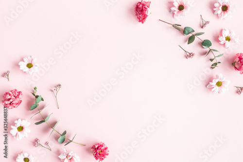 Flowers composition. Pink flowers and eucalyptus branches on pink background. Valentines day, mothers day, womens day concept. Flat lay, top view
