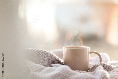Photo Cup of coffee and knitted sweater near window in morning