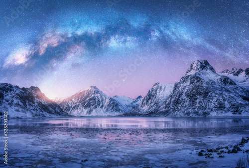 Foto Milky Way above frozen sea coast and snow covered mountains in winter at night in Lofoten Islands, Norway