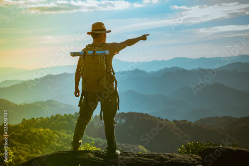 Stampa su Tela Young Man standing alone in forest outdoor with sunset nature on background Travel Lifestyle and survival concept