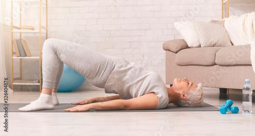 Fotografie, Obraz Active senior woman doing back exercise on floor at home