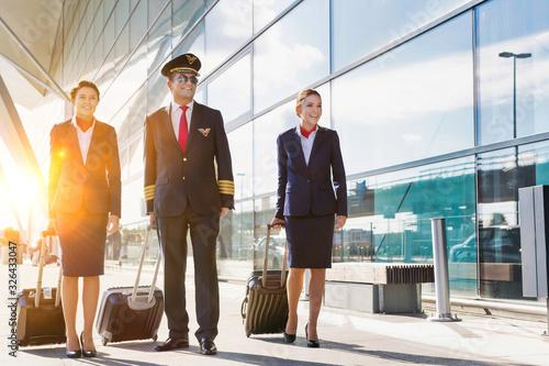 Mature pilot with young beautiful flight attendants walking in airport Fototapeta