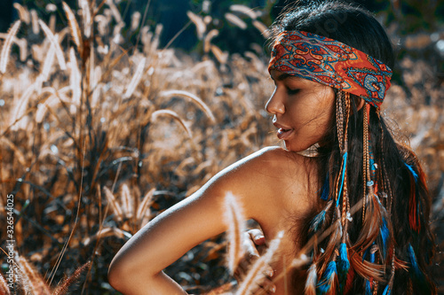 фотография beautiful young hippie style woman close up portrait at sunset on a field