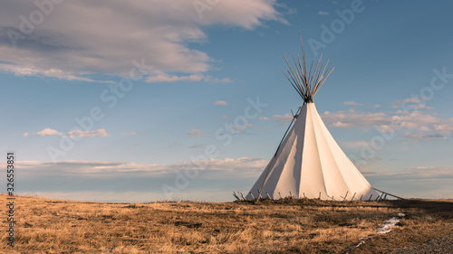 Photo Traditional Native American nomadic teepee in the grassy plains at sunset and be